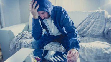 Spanisches Betäubungsmittelstrafrecht: Man sitzt verzweifelt vor einem Tisch mit Drogen