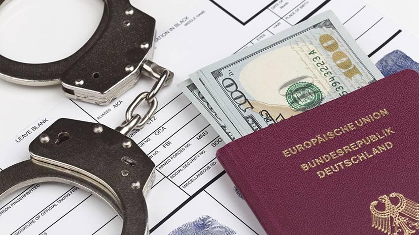 EU-Haftbefehlsrecht: Handschellen und ein Reisepass mit Dollarn auf einem Tisch