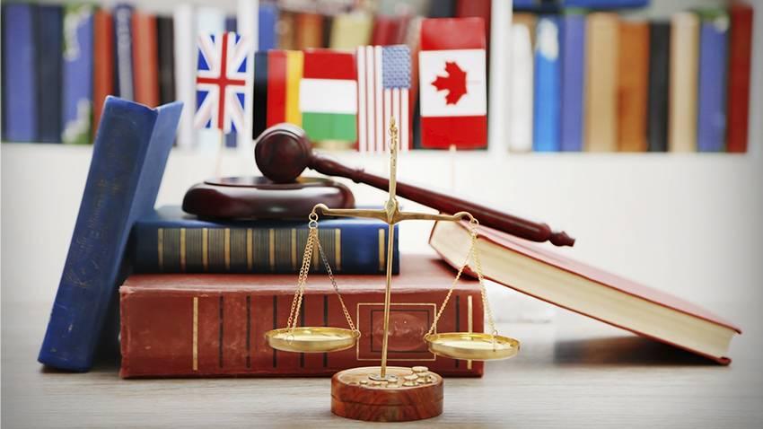 Internationale Strafverfahren: Gerechtigkeitswaage steht vor Büchern, Gerichtshammer und einigen internationalen Länderflaggen