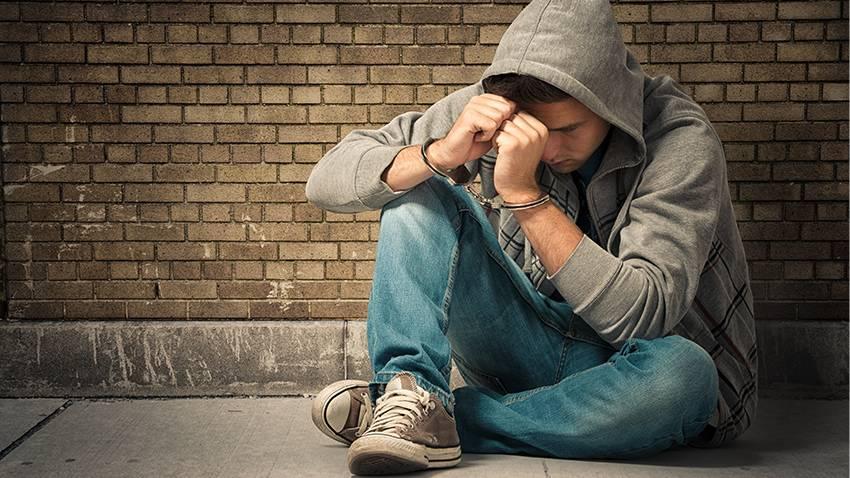 Spanisches Jugendstrafverfahren: Jugendlicher sitzt verzweifelt mit Handschellen auf dem Boden
