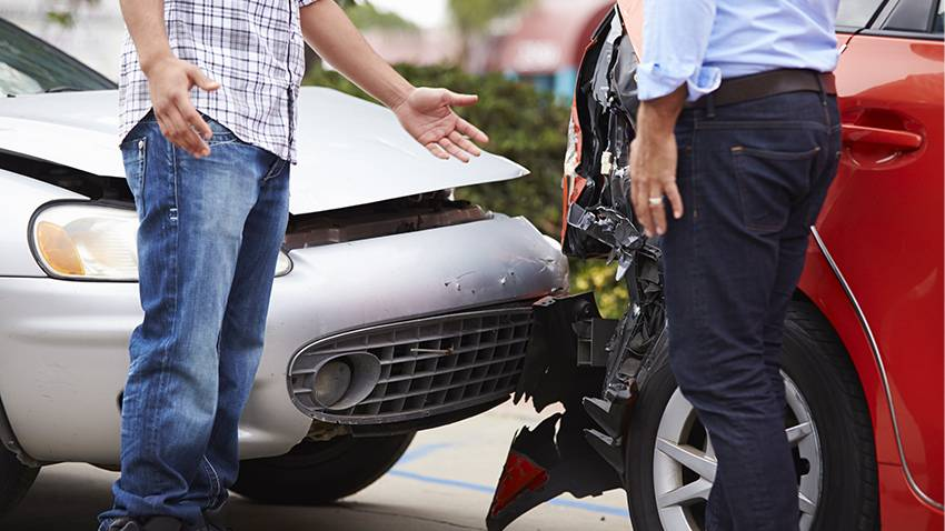 Spanisches Verkehrsstrafrecht: Zwei Männer begutachten Auffahrunfall